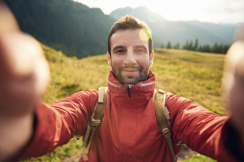 Man, i att fotvandra kugghjulet som utanför tar en selfie arkivbild