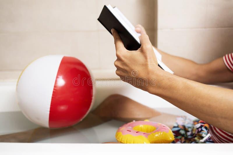Man i baddräkt som läser en bok i badkaret arkivfoto