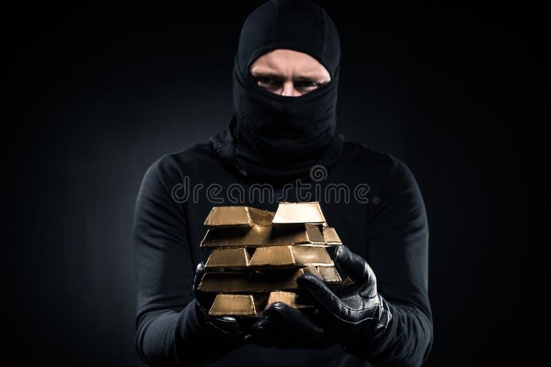 Man i balaclavaen som rymmer guld- guldtackor arkivbilder