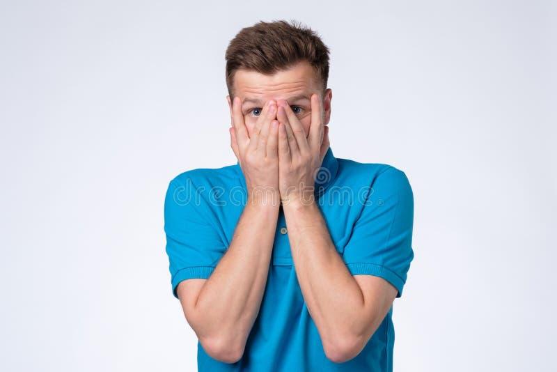 Man i blå framsida för t-skjorta nederlagräkning med händer som ser blyga arkivfoton
