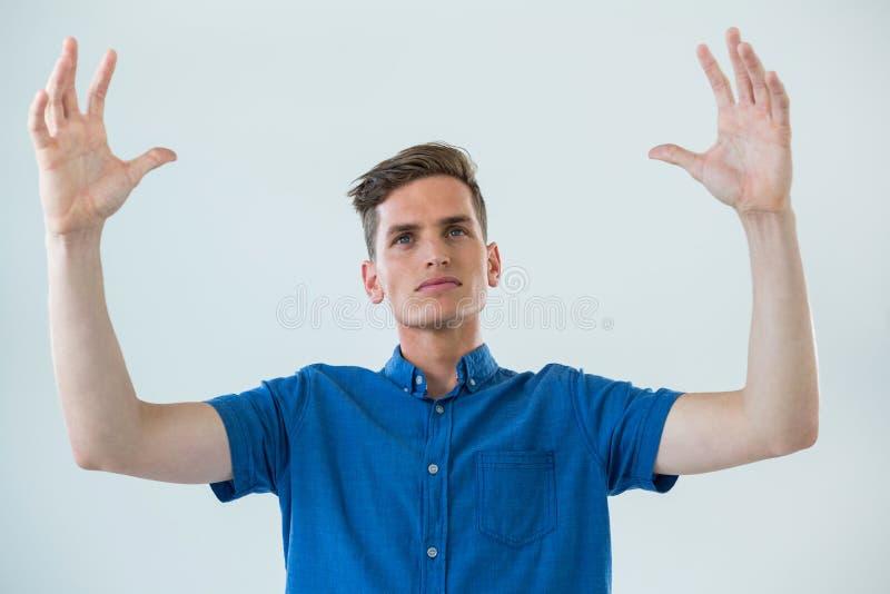 Man i blå skjorta med lyftta armar royaltyfria foton