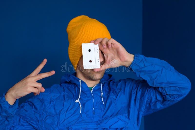 Man i bl?tt omslag f?r tappning och gul hatt med ljudbandet arkivfoto