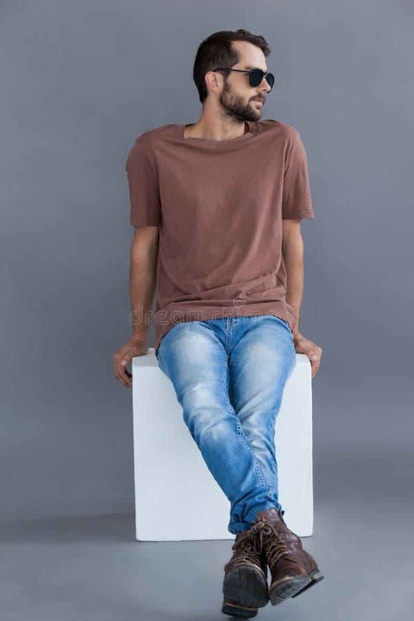 Man i brun t-skjorta och solglasögon som sitter på ett kvarter arkivbilder
