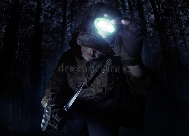 Man i den dräktomslaget, handskar och kniven som vänder på huvudficklampan arkivfoton