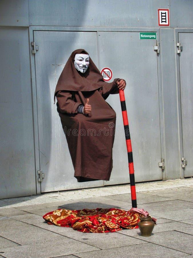 Man i den Guy Fawkes maskeringen på gatan som gör hans få att sväva trick fotografering för bildbyråer