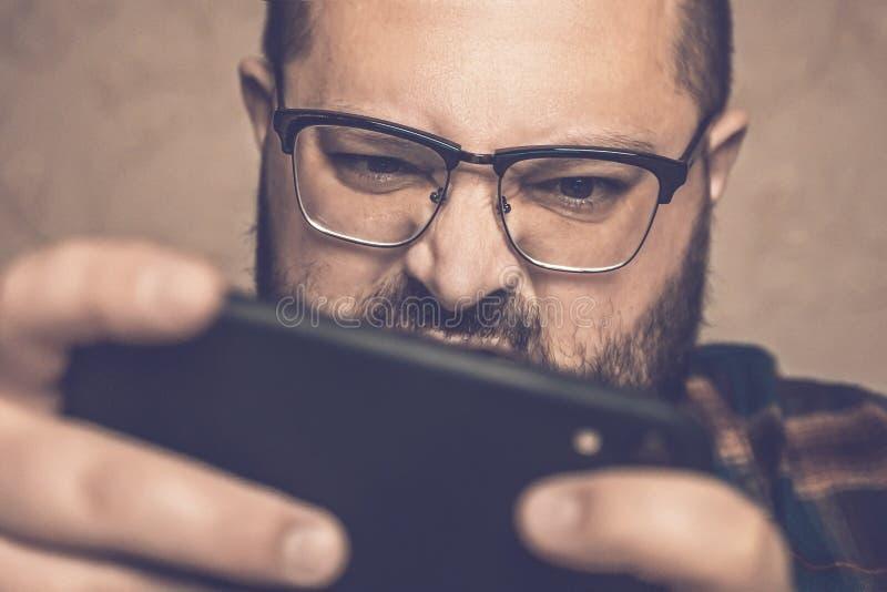 Man i den ilskna spela mobila videospelet för exponeringsglas som rymmer smartphonen vid båda händer royaltyfria foton