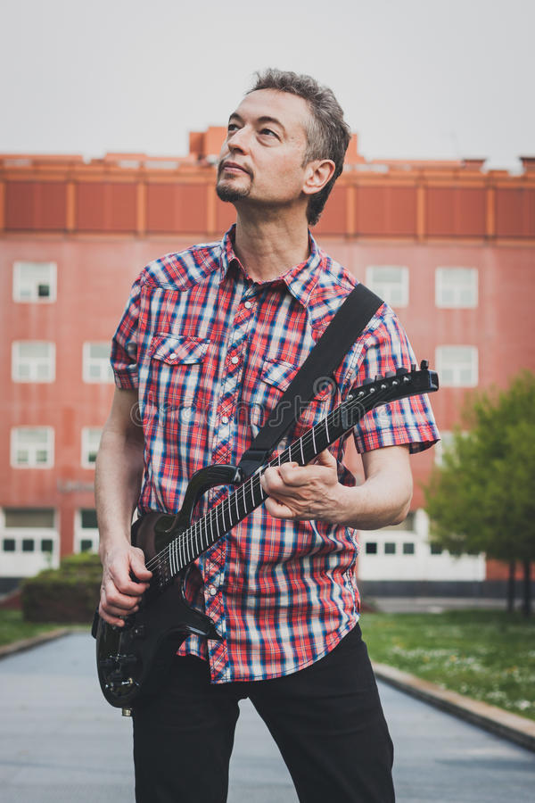 Man i den korta muffskjortan som spelar den elektriska gitarren royaltyfri foto