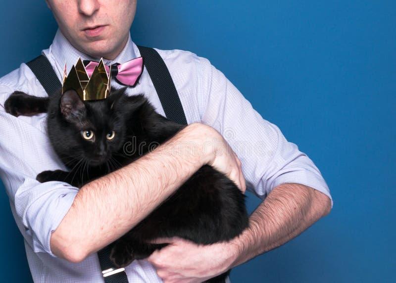 Man i den rosa skjortan, suspenderen och flugan som rymmer den gulliga svarta katten i skinande guld- krona på blå bakgrund med k royaltyfria bilder