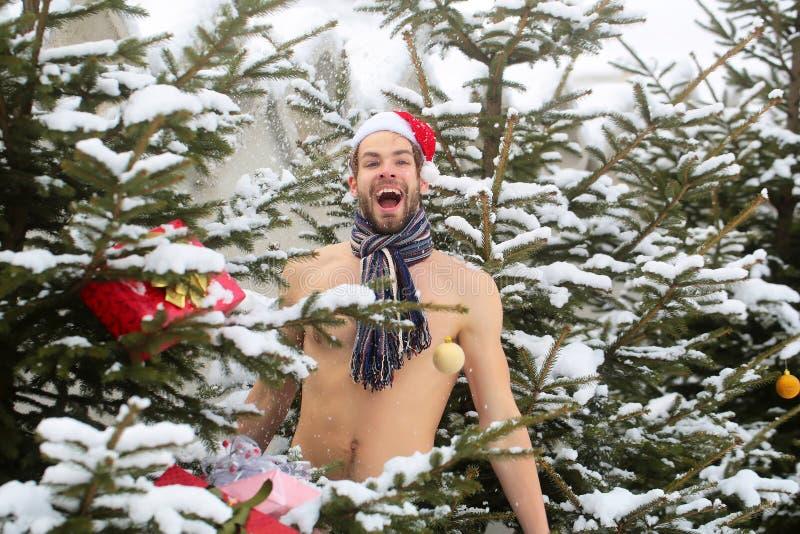 Man i den santa hatten och halsduken som torkar med sn? arkivfoton