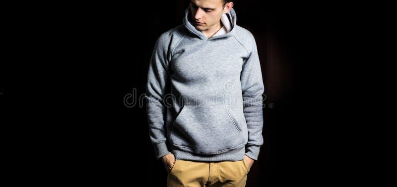 Man i den tomma gråa hoodien, tröja på en svart bakgrund, åtlöje upp, fritt utrymme royaltyfria foton
