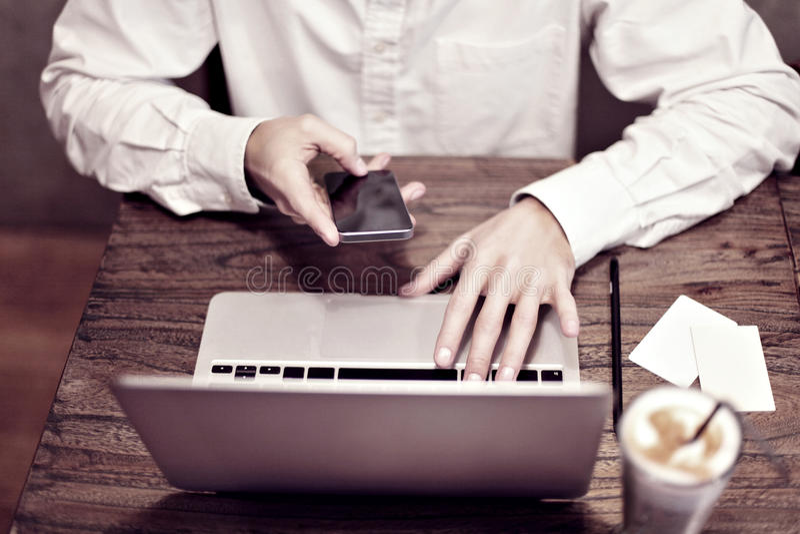 Man i den vita skjortan som arbetar på den bärbara datoren och dricker latte i ett kafé eller coworking Fokus på handen och tange royaltyfri foto