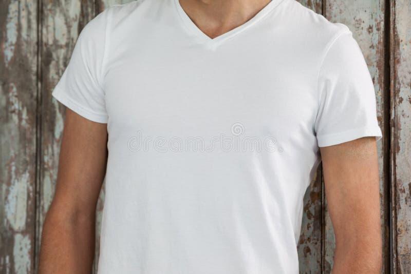 Man i den vita t-skjortan mot träbakgrund royaltyfri fotografi