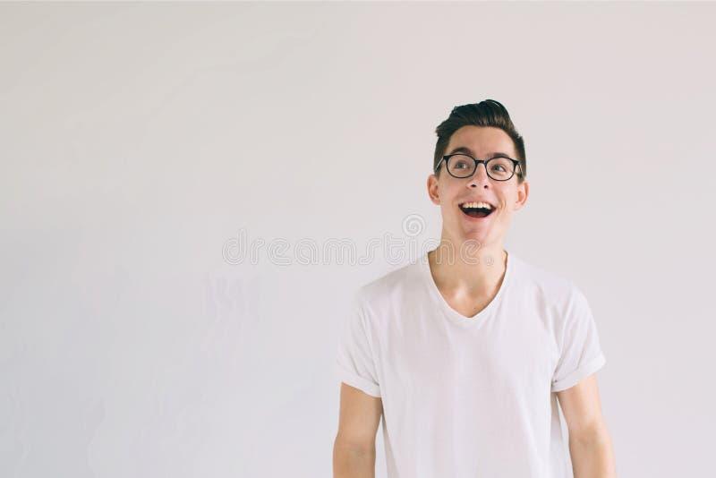 Man i den vita t-skjortan och exponeringsglas med stort leende som isoleras på vit bakgrund En mycket snäll student har ett bra l fotografering för bildbyråer