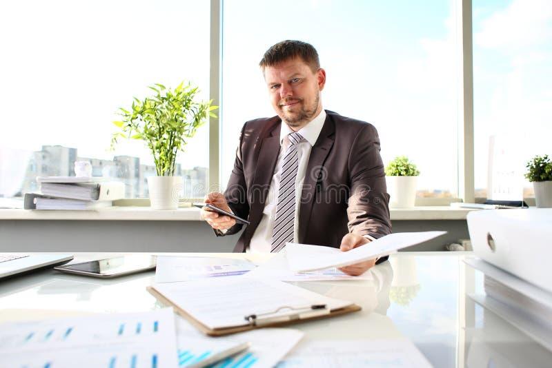 Man i dräkt- och bandhåll i armlegitimationshandlingar på kontoret royaltyfri bild