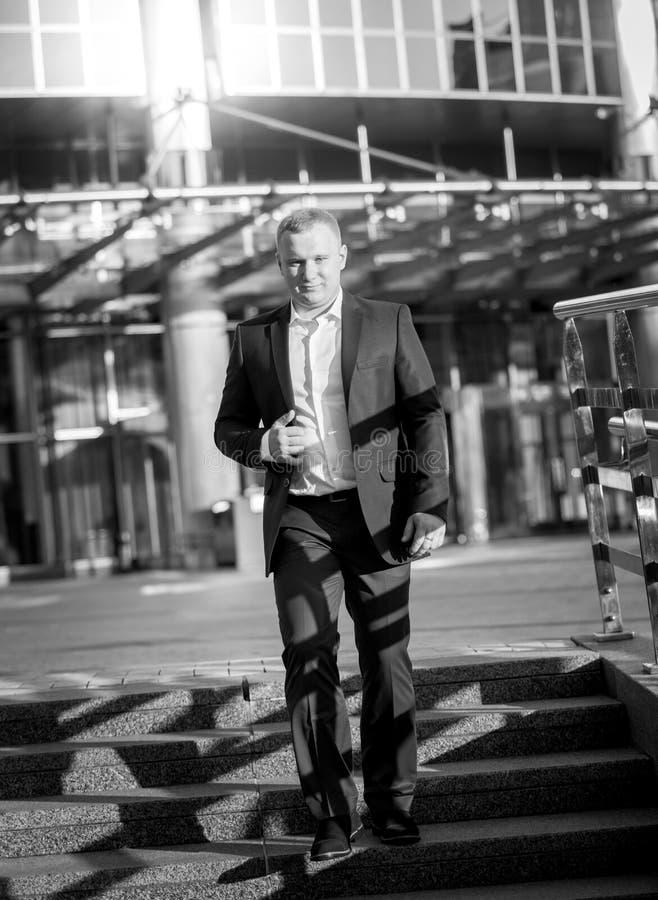Man i dräkt som går ner trappan på affärsbyggnad arkivfoto