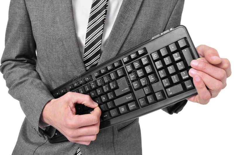 Man i dräkten som spelar ett datortangentbord royaltyfri foto