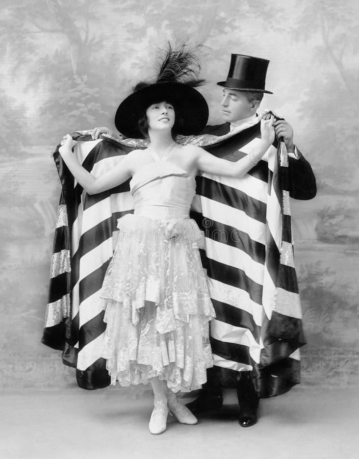 Man i en bästa hatt som hjälper en kvinna in i en udde (alla visade personer inte är längre uppehälle, och inget gods finns Lever fotografering för bildbyråer
