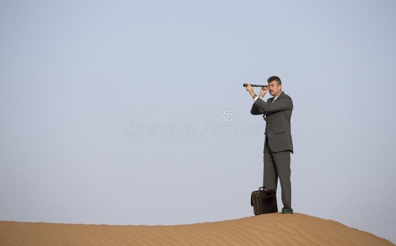 Man i en dräkt i en öken med en kikare fotografering för bildbyråer