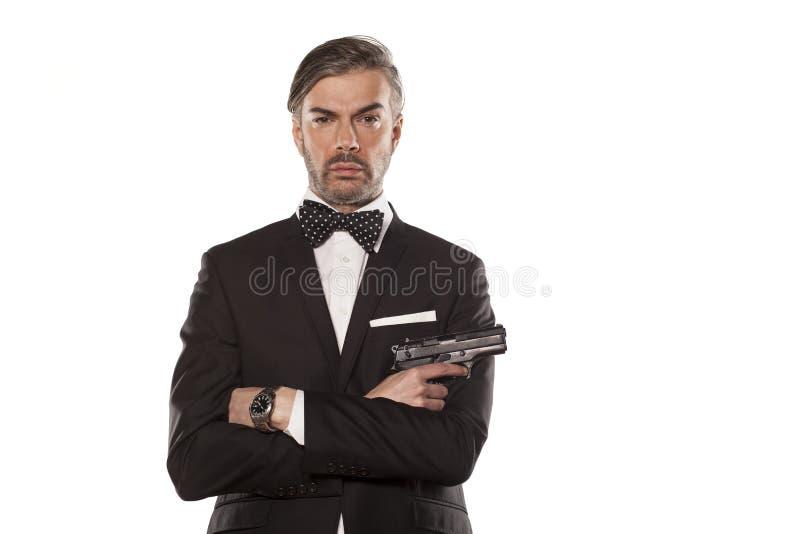 Man i en dräkt med ett vapen royaltyfri bild