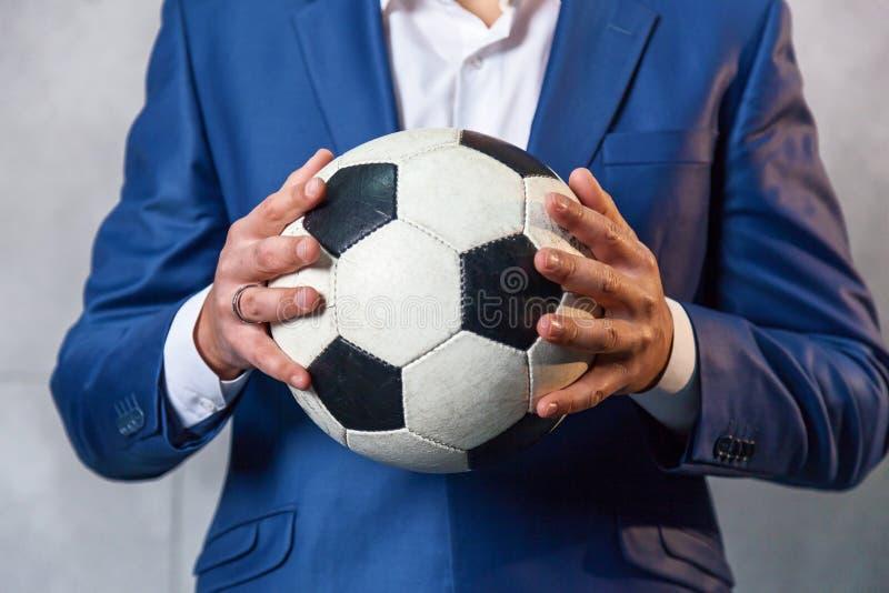 Man i en dräkt med en fotbollboll arkivbild