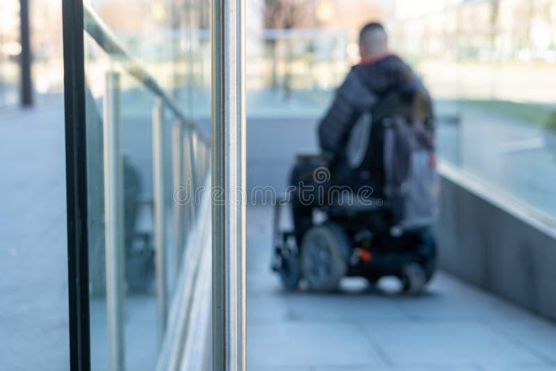 Man i en elektrisk rullstol genom att använda en ramp i suddighet royaltyfria bilder