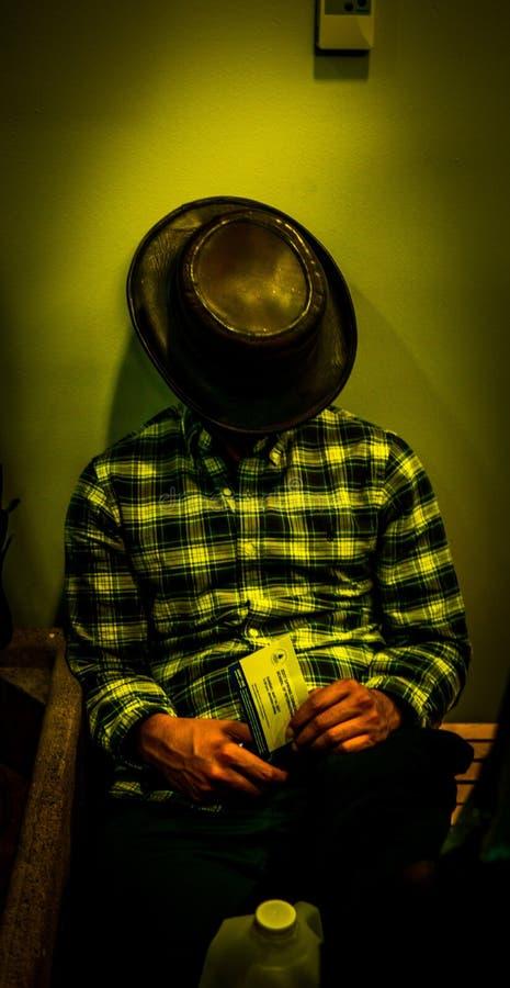 Man i en flanellskjorta och en cowboyhatt som sover, medan sitta nära en vägg arkivfoton