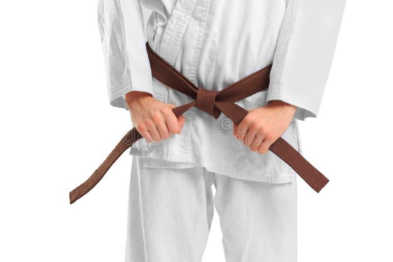Man i en kimono och ett bälte för kampsporter på den vita bakgrunden royaltyfri fotografi