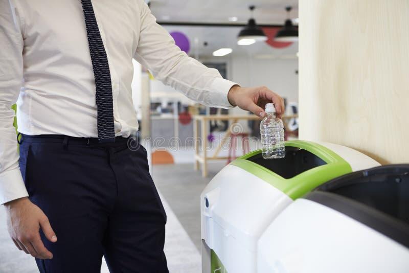 Man i en plast- flaska för kontorsåtervinning, slut upp royaltyfria bilder