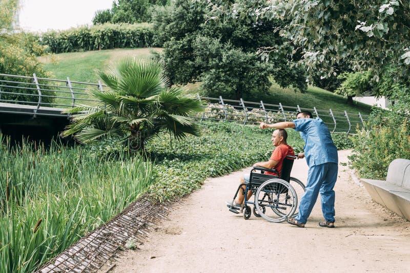 Man i en rullstol som talar med hans vaktmästare royaltyfri fotografi