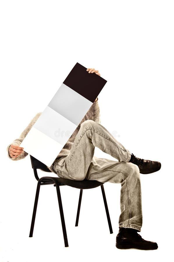 Man i en stol med en tidskrift royaltyfria foton