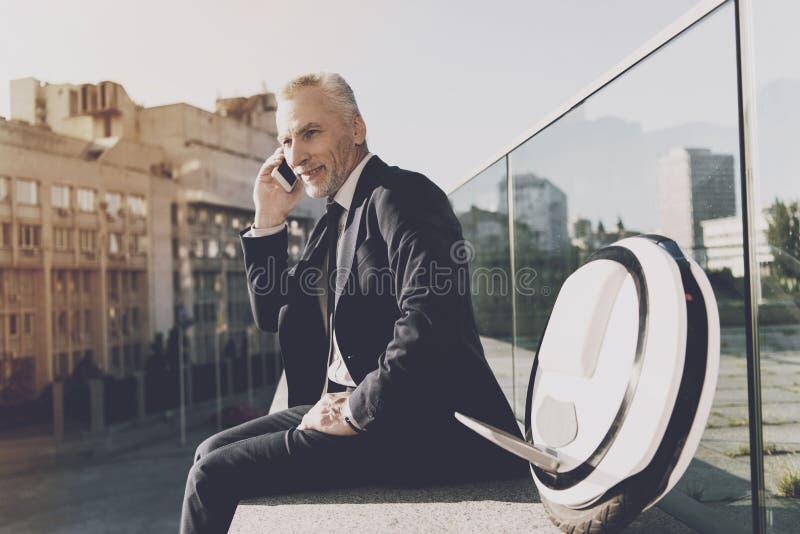 Man i en svart dräkt som talar på telefonen royaltyfria bilder