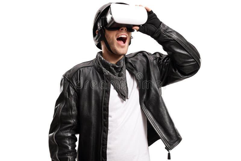 Man i ett läderomslag som håller ögonen på på en VR-hörlurar med mikrofon royaltyfri bild