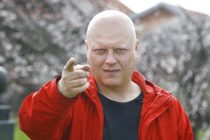 Man i ett rött omslag som hotar med fingret och varningar arkivbilder