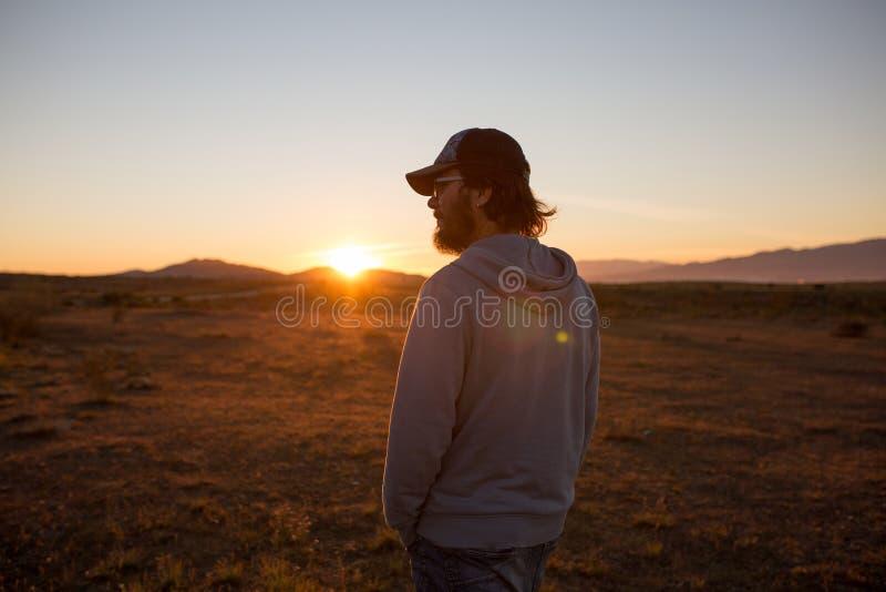 Man i ett ursprungligt landskap under en härlig flammande solnedgång arkivbild