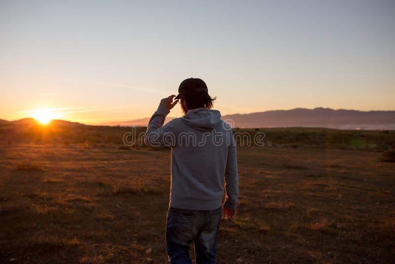 Man i ett ursprungligt landskap under en härlig flammande solnedgång royaltyfri foto