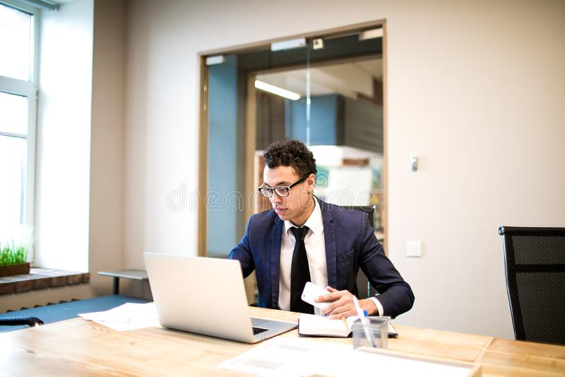 Man i för entreprenörläsning för dräkt och för exponeringsglas kompetent nyheterna via netbook royaltyfri fotografi