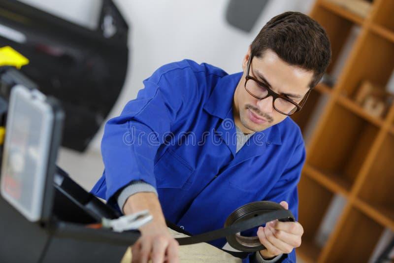 Man i garage med mekaniska delar royaltyfria foton