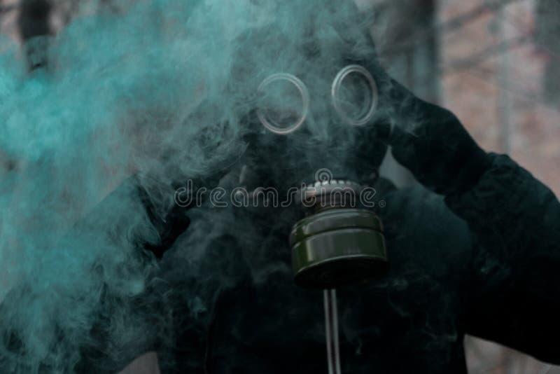 Man i gasmask mot katastrofbakgrund Oljetrumma och världsöversikt royaltyfria bilder
