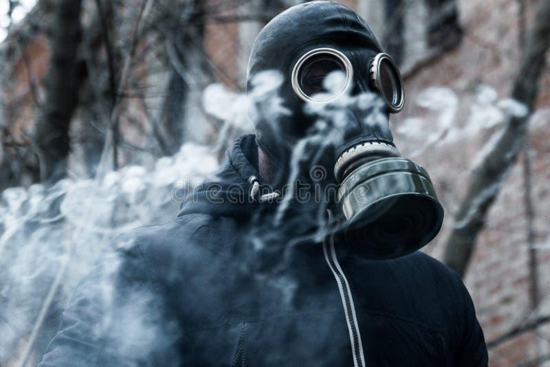 Man i gasmask mot katastrofbakgrund Oljetrumma och världsöversikt arkivbilder