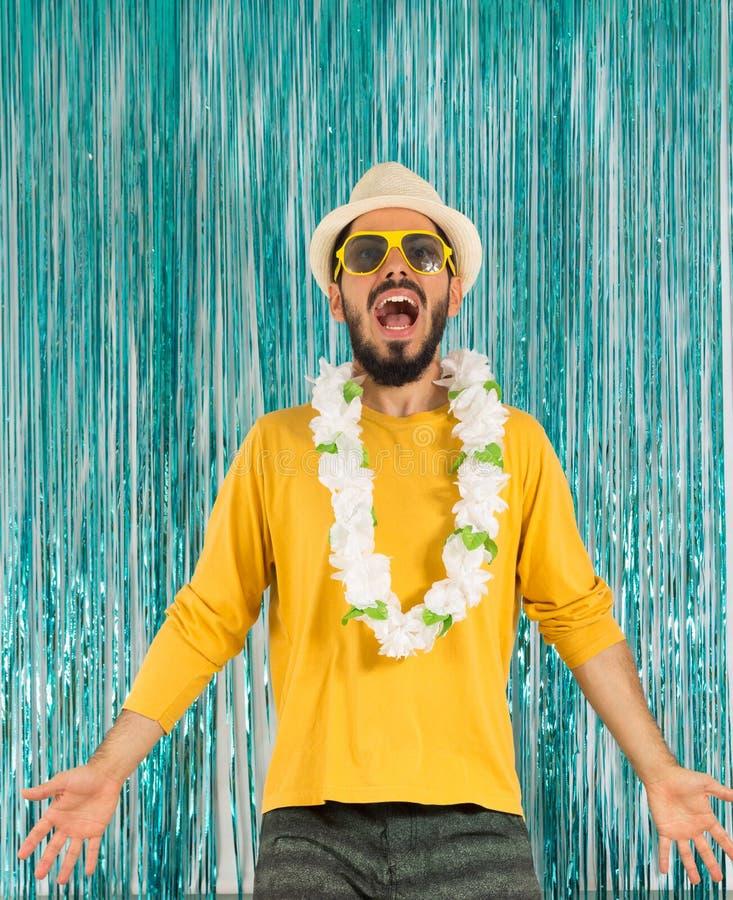 Man i gräsplan- och gulingkläder, solglasögon och hawaiansk necklac royaltyfri bild