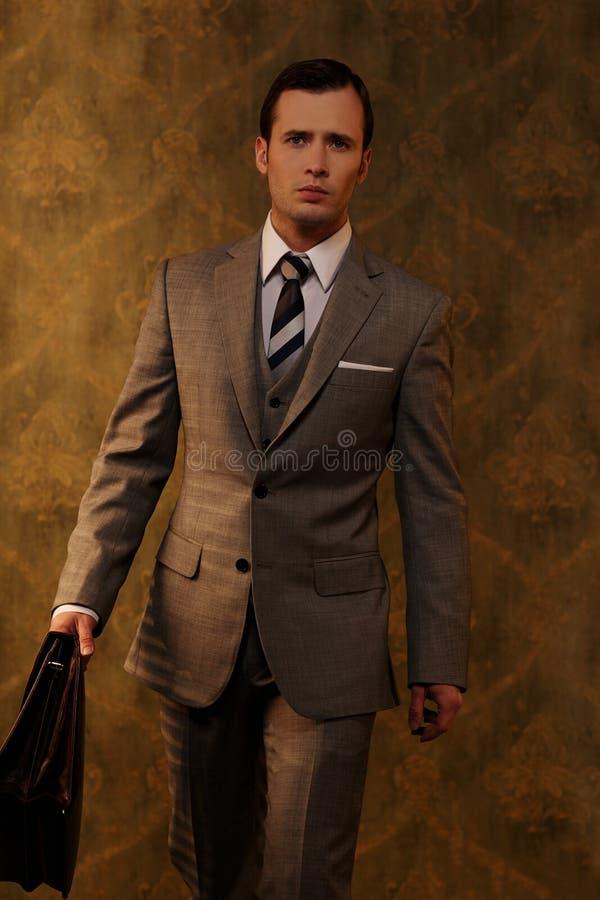 Man i grå dräkt med en portfölj royaltyfri bild