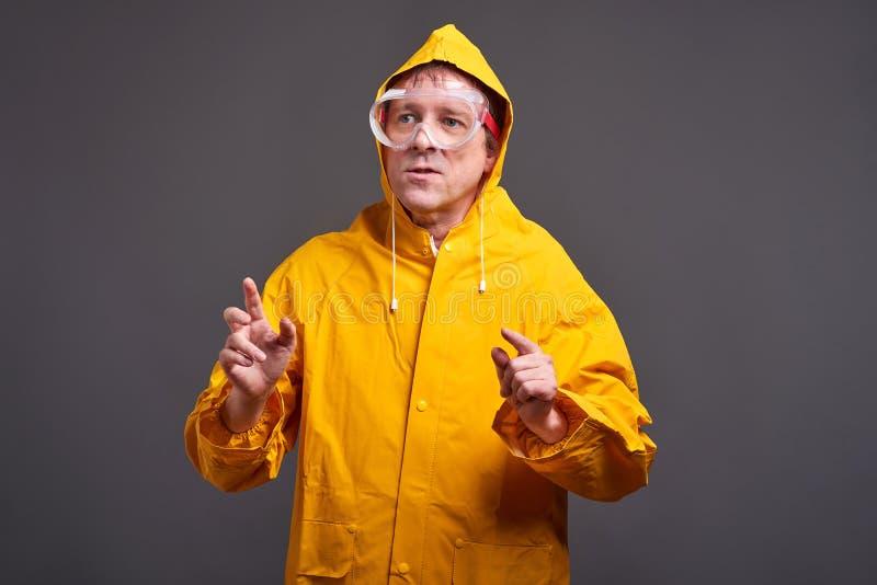 Man i gul regnrock royaltyfri fotografi