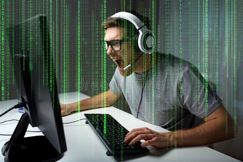 Man i hörlurar med mikrofon som hemma spelar datorvideospelet arkivbild