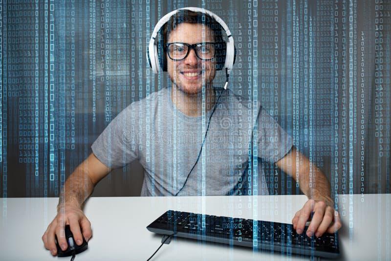 Man i hörlurar med mikrofon som hemma spelar datorvideospelet royaltyfri bild