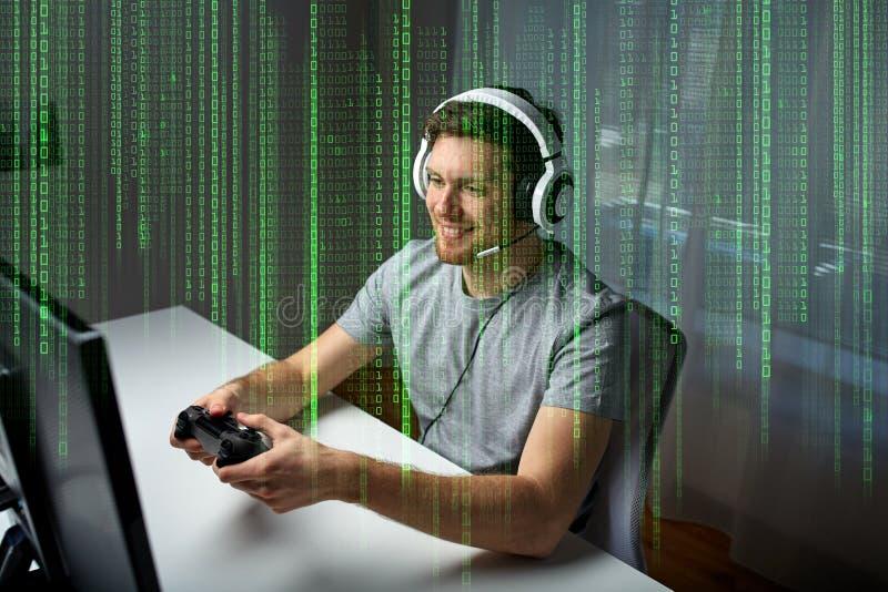 Man i hörlurar med mikrofon som hemma spelar datorvideospelet arkivfoto
