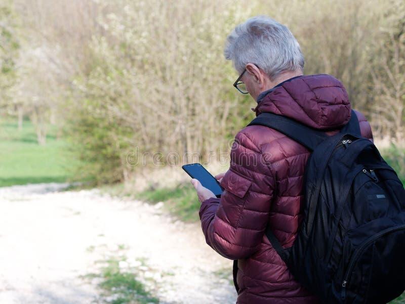 Man i hans seventies som ser hans smartphone royaltyfri fotografi