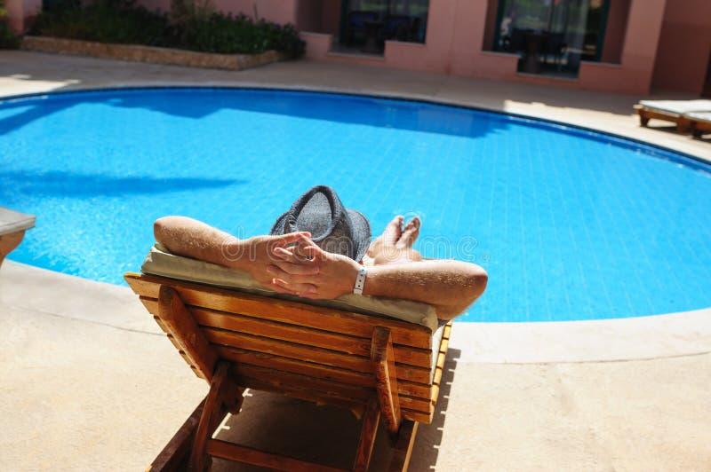Man i hatt som solbadar på en soldagdrivare vid pölen royaltyfri bild