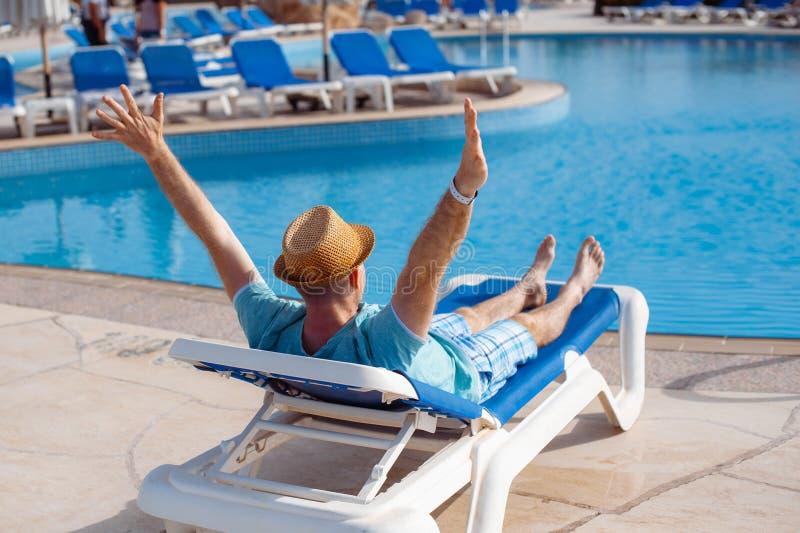 Man i hatt som solbadar på en soldagdrivare vid pölsommaren Begrepp av loppet och att vila arkivbilder