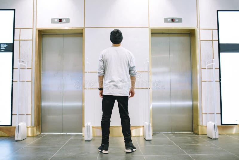 Man i hattanseende nära hissen royaltyfria bilder