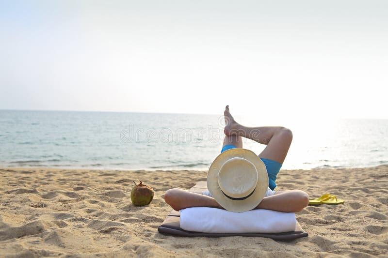 Man i hatten med kokosnötcoctailen på stranden royaltyfria foton